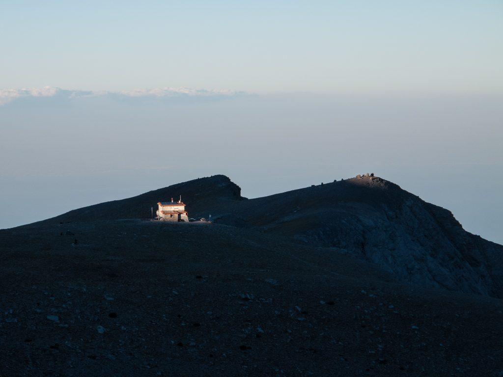 A beautiful light beam from the setting sun illuminates the Kakkalos Refuge as we return.